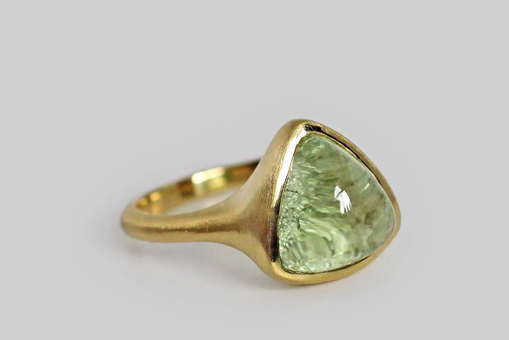 Soothing and glowing, a misty, cucumber-green tourmaline cabochon sits, nested, inside a thick-walled, organic bezel, which tapers seamlessly into its ring's integral shank. This bubbly, triangular, tourmaline gem has been cleverly cut, leaving the natural, crystalline texture of its terminus intact on the bottom side— the gem's smooth high dome magnifies this rough crystal texture to magical effect!
