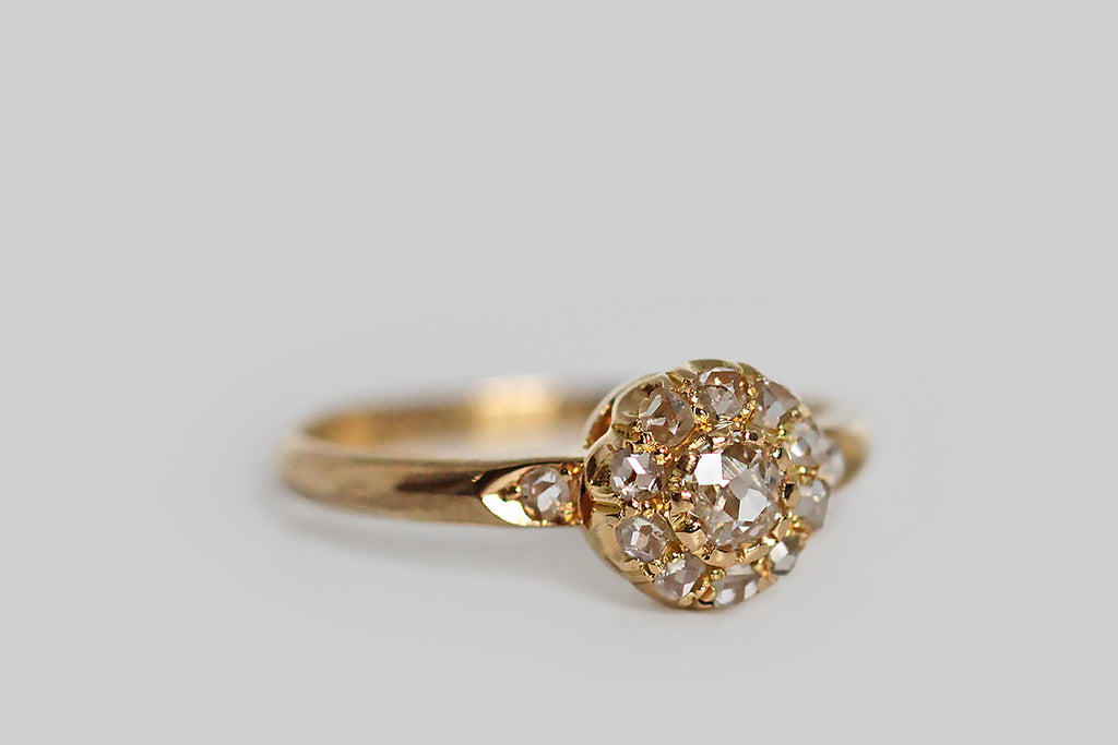 A Victorian era engagement ring, modeled in 18k yellow gold, whose central gem is a .20 carat old mine cut diamond. This soulful old stone is mounted in the ring's crownlike head, where it is surrounded by a halo of ten, smaller, rose cut diamonds. Two further rose cuts adorn the ring's epaulette shoulders.