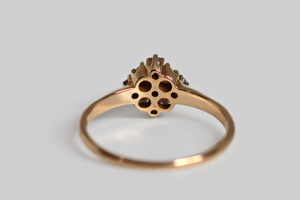 A late Victorian diamond and seed pearl cluster ring, with outstanding proportion and balance. This dainty love is modeled in 14k yellow gold. Its head is a thoughtfully-made, equilateral diamond, that holds within it the ring's five white diamonds and four natural seed pearls. There is a subtle cruciform shape implied by the diamond layout, and the ring's centermost prongs come together to give the impression of small flowers. The ring's  integral, half-round shank tapers toward the base.