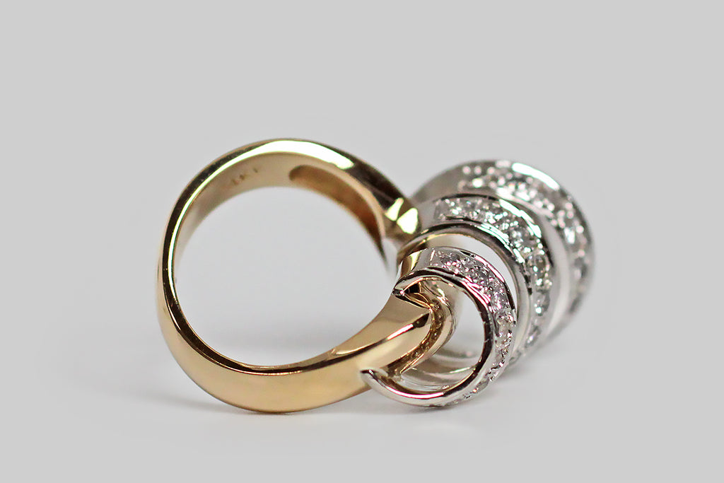 A vintage modernist ring, modeled substantially in 14k gold, whose unusual figure can be compared to a diamond-encrusted cyclone. The ring head's open, spiraling white gold form whorls around a weighty, diagonally-placed, yellow gold rod— the graduating white gold form is highly-dimensional and is enlivened by many bead-set white diamonds.