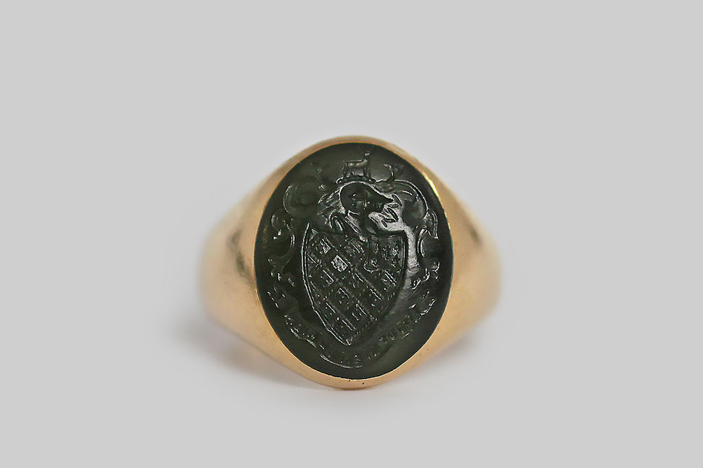 "A vintage signet ring, with a classic tapering profile, whose flush-set, oval, jade gem is carved with a heraldic shield, and a french motto that translates to ""do it well, or not at all."" This intaglio is expertly rendered, with fine crisp details, including the shield, a knight's helmet, a small central animal (a deer), the motto banner, and a motif of vining ivy."