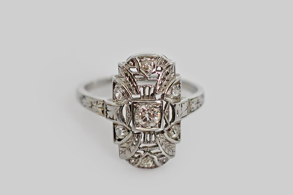 A charming, Art Deco era shield ring, with a delicate appearance. This little shield is modeled in 18k white gold— it is decorated with architectural, milgrained, knife-wire elements, as well as fine engraved details that adorn its shoulders (a ginko leaf, an orange blossom) and four engraved, folate, plumes that fan out, from behind the central old European cut diamond, across the ring face.