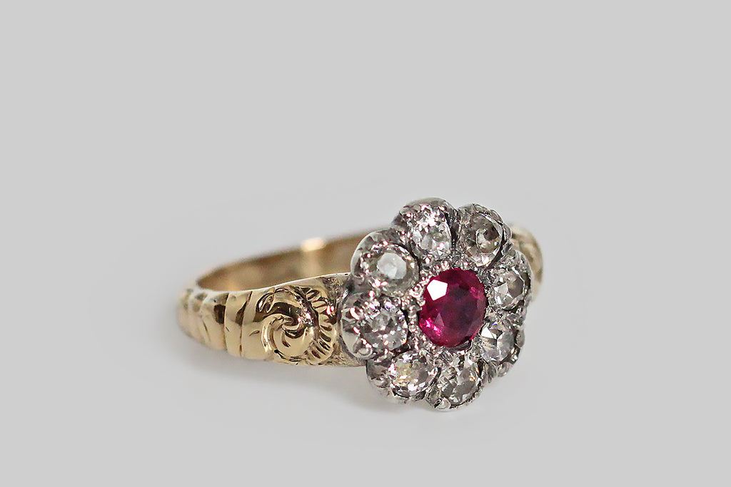 A soulful, Georgian-era, flower-form ring, modeled in 18k yellow gold with a silver top. This ring's eight, oval, collet-set, old mine cut diamonds are arranged around its vibrant, untreated, central ruby. The shoulders of the ring are decorated with voluptuous, swirling repoussé work, that is typical of the period. This ring has a closed back, and its weighty, half-round shank tapers toward the base.
