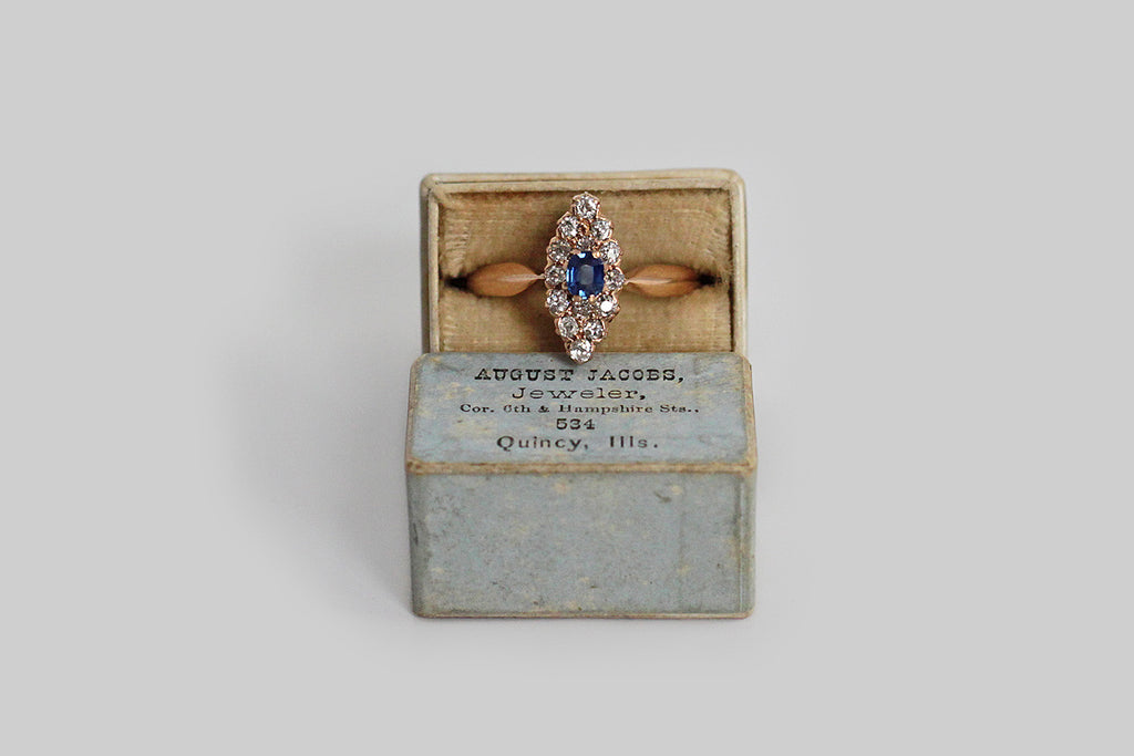 A darling turn of the century diamond and sapphire navette ring, made in rosy 14k gold. This little boat is encrusted with approximately 1/2 carat of close-set, old mine cut diamonds that come together to create a glittering audience around the natural, cushion cut, blue sapphire. The sapphire is a vibrant, medium-blue color. Lovely proportions exist between the ring's navette head and the shapely shank. The scalloped cutwork gallery adds a fine, subtle, detail. This would make a wonderful engagement ring f
