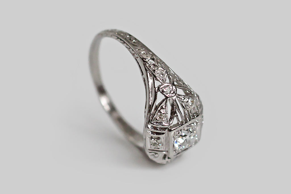 An early 20th century engagement ring, modeled in platinum, whose primary gem is a .38 carat old European cut diamond. This eye-shaped ring is softly-bombe and brimming with beautiful details— delicate knife-wire sections flank the central diamond's squarish seat, and languid, diamond-set bows decorate the ring's shoulders. Additional bead-set diamonds add sparkle to the gallery.