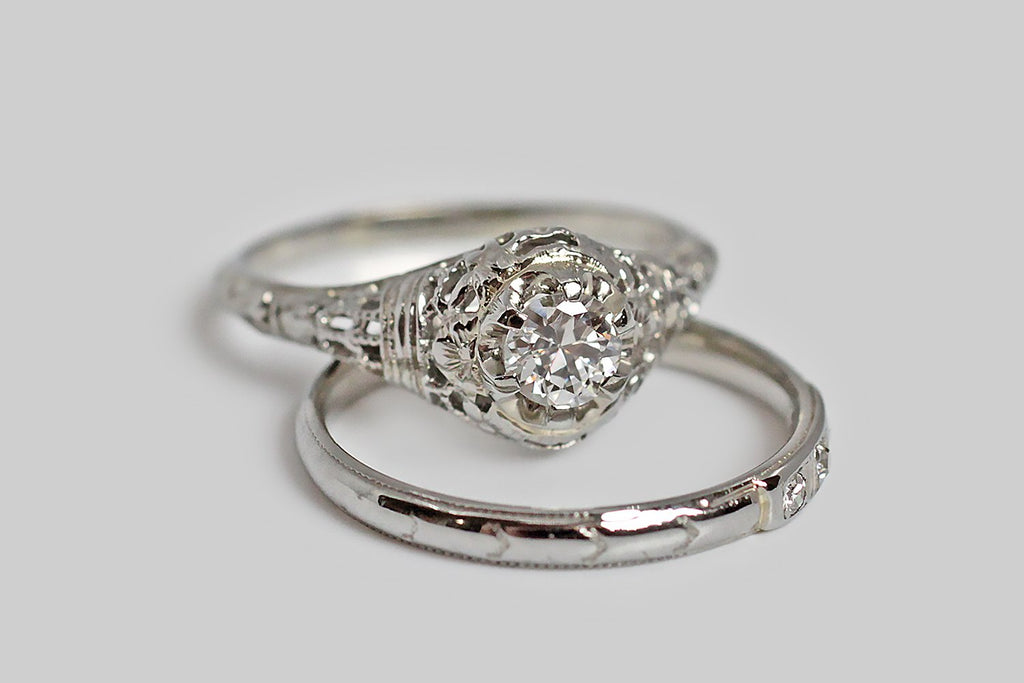 An Art Deco era engagement ring, with a slender bombe profile, whose 18k white gold setting is a floral-inflected filigree. This decor is an arrangement of milgrain lattice work, high polish binding ribbons, and romantic orange blossoms— the orange blossom shape is mirrored in the scalloped edges of the ring's six prong buttercup mount. A very pretty, half carat, early-modern-brilliant-cut diamond is set securely into these six prongs.