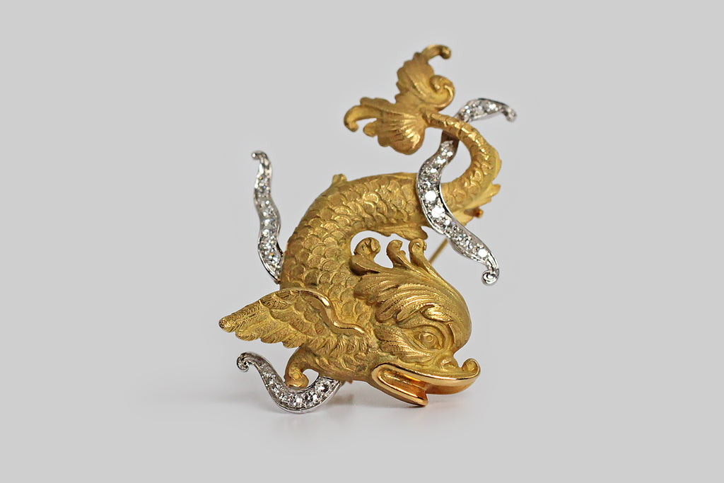 An impressive vintage brooch, depicting a plumed dolphin, made in the mid twentieth century to reflect the style of the Victorian era. This lovely creature is modeled in 18k yellow gold; the ribbon banners that float about his tail and wing are made in platinum and set with diamonds. This is the form all dolphins took earlier in history— people imagined them as friendly sea serpents who rescued sailors in peril. For this reason dolphins represent swiftness, charity, and love. This sweet creature is extra la