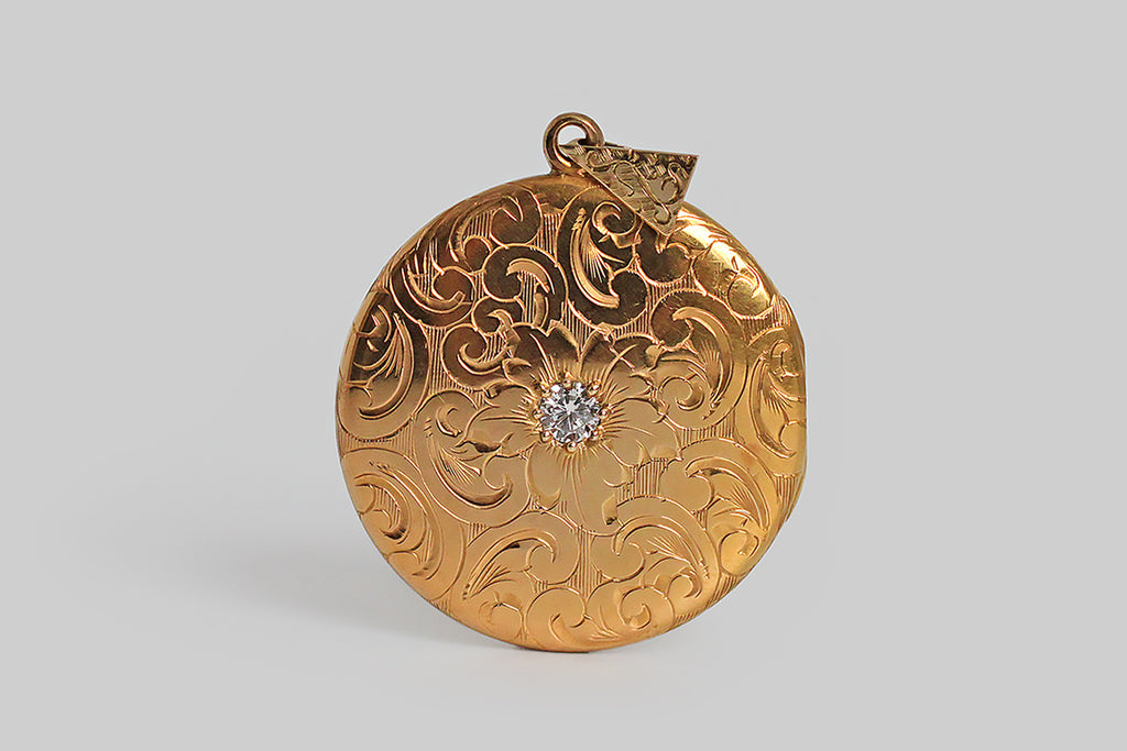 An extra-large, Victorian era locket, modeled in high-color 14k yellow gold, whose face is set with a sparkling 1/3 carat white diamond. The locket is decorated, edge-to-edge, front and back, with ornate, hand-engraved plumes and curls. A plump, languid flower rests amid these swirling forms, at the center of the locket's face, where the diamond marks its center. This is an especially lovely old locket— the hand engraving is deep, confident, and expressive.