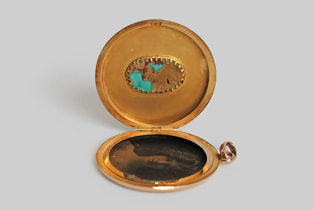 An extra-large, round, Victorian era locket, modeled in 14k rosy yellow gold, whose face is set with a single, large, matrix-webbed turquoise cabochon. This soulful, oval, blue-green gem is highly saturated, and its matrix is reddish-to-golden brown. This locket is clean, minimal, and almost contemporary felling— the earthy turquoise gem seems to float in the simple, gold pool of the locket face. The locket's reverse is hand-engraved with a large monogram, in period script