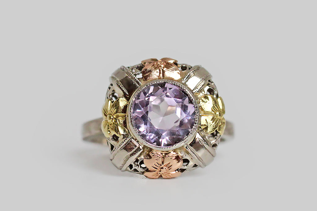An Art Deco, filigree, dinner ring, modeled in three colors of 14k gold, and intended to recall a flower basket. This playful design features four, four-petaled blossoms (two vibrant yellow gold, and two rose gold) stationed to the north, south, east and west of the ring's central, Rose de France, amethyst gem. This large, round amethyst is a cheerful, highly-saturated lavender color