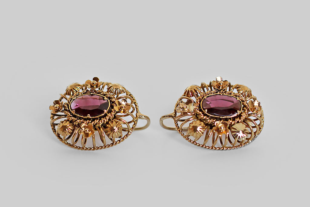 A pair of Victorian-era drop earrings, modeled in 14k yellow gold, each one a fascinating wire cage, constructed with both round and twisted gold wire, and dotted with three-dimensional, hand-built flowers. These earrings have faceted, purplish-red, rhodolite garnets, at their centers. The garnets are held in a modified bezel with six tab-style prongs. Earwires are integral French hooks with a c-shaped catch. These earrings are very flattering in wear and they are brimming with fine details.