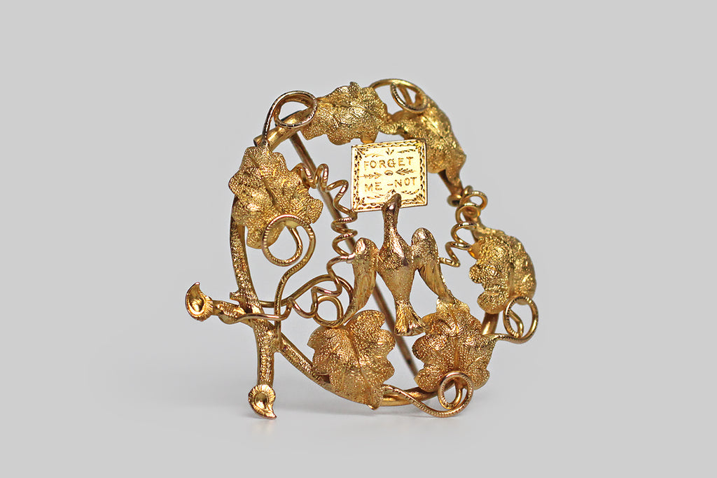 "A large, Georgian-era brooch, modeled in 14k yellow gold, whose subject (a dove in flight, bearing a letter) is depicted among grapevines, grape leaves, and tendrils. Our feathered friend's message is a sentimental one— ""forget me not."" This brooch is primarily repoussé, which means its many, highly-dimensional elements were formed by hammering a gold sheet into relief from the reverse side."