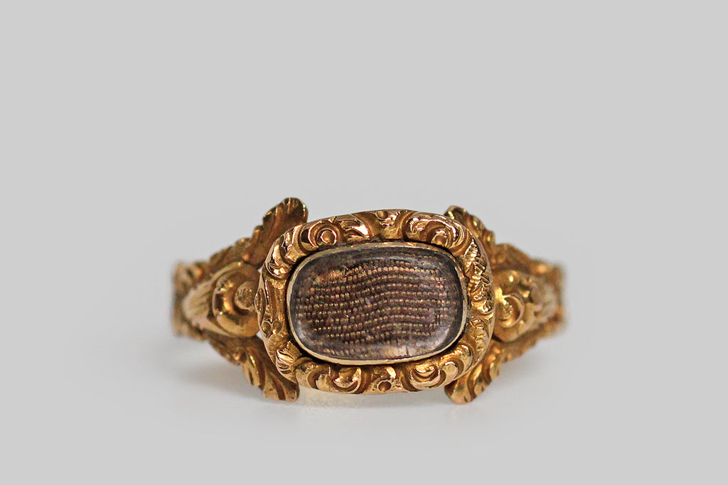 A dainty, Georgian-era mourning ring, modeled in high karat gold and decorated with the sumptuous, chased, floral details that are typical of this period. The ring's highly dimensional shoulders each feature a stylized cabbage rose and a pair of leaves stretching out above it to create the impression of a split shoulder. This shoulder decor is especially voluptuous and creaturely— the ornate bezel that rests betwixt the roses holds tightly plaited locks of human hair,