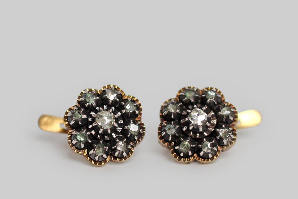 A rare and wonderful pair of dainty, Georgian, button earrings, fabricated in 14k yellow gold and silver, whose rose cut diamonds are arranged to suggest a flower. These glinty old diamonds are mounted in crimped, darkened silver collets, and those collets rest inside gold, flower-shaped, sawtooth-edge bases. The subtly-convex backsides of these earrings are decorated with the most beautiful, deeply-hand-engraved details