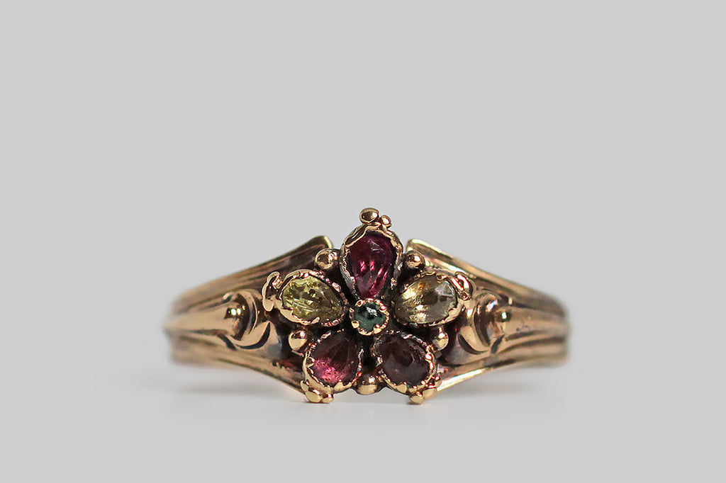 "A Georgian-era pansy form ring, modeled in high karat gold, whose petals are set with faceted garnet and chrysoberyl gems. This little flower is highly-dimensional, thanks to the slight pitch of its petals, and the alternating colors of these petals add a loves me, loves me not suggestion to this traditional sweetheart motif. The ring's ornate split shoulders and reeded shank are shapely, unusual, and joined by a delicate shell-like medallion. Pansy is the ""think of me"" flower,"