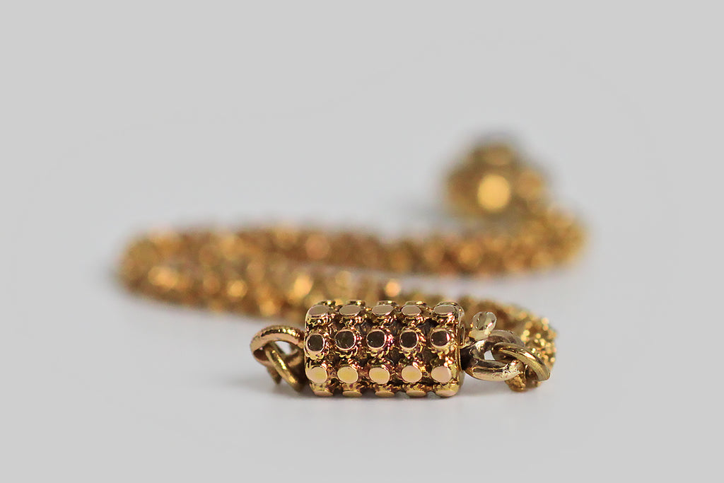 A rare and wonderful Georgian-era bracelet, whose dainty 22k gold links are each decorated with a pair of six-petaled flowers. These high-color, flower-form links encircle the wrist giving the impression of a golden garland. Our garland bracelet also features a miniature heart-shaped locket— the front side of this tiny heart is ornately hand-engraved with baroque plumes, and set with a deep-red garnet.