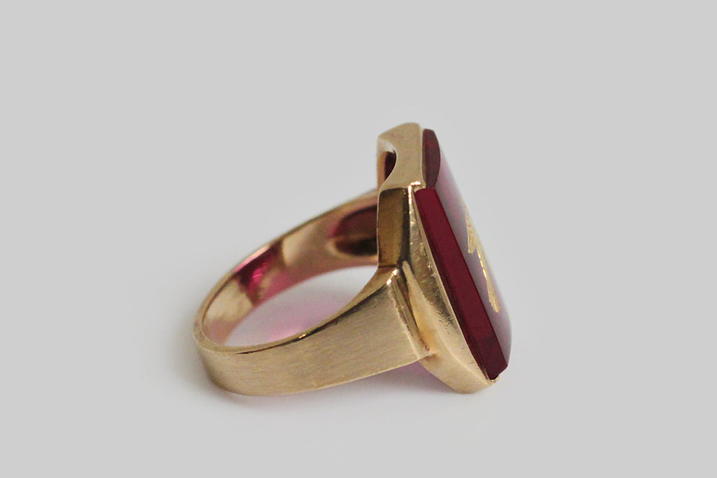 A handsome, Art Deco era signet ring, made in 10k yellow gold and featuring a large, intaglio-carved, created ruby. The subject of this intaglio carving is a songbird in flight, who can be seen as diving or rising, depending on your perspective. Our songbird is centered in the vibrant field of color and is beautifully gilded.