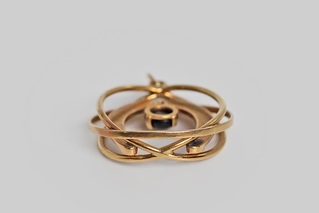 "A large and especially cool vintage charm, made in 14k yellow gold and featuring a large horseshoe that bears the phrase ""good luck,"" where its nails would usually be. This substantial lucky charm hangs inside an arrangement of three overlapping rings that suggest movement and give the piece an atomic vibe. A black star sapphire rests, in prongs, at the center of the arrangement."
