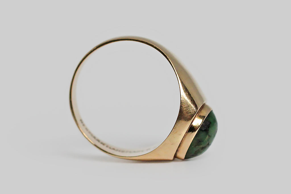 A sleek, mid-20th-century, Danish modernist ring, set with a character-rich green turquoise cabochon. This gem is held in a smooth, round bezel, that sits atop the very-slightly-larger cushion-shaped ring face— a subtle design element that makes this ring a little unusual and that gives its design a geometric focus. The ring's wide, smooth shank tapers from the shoulder toward the base.