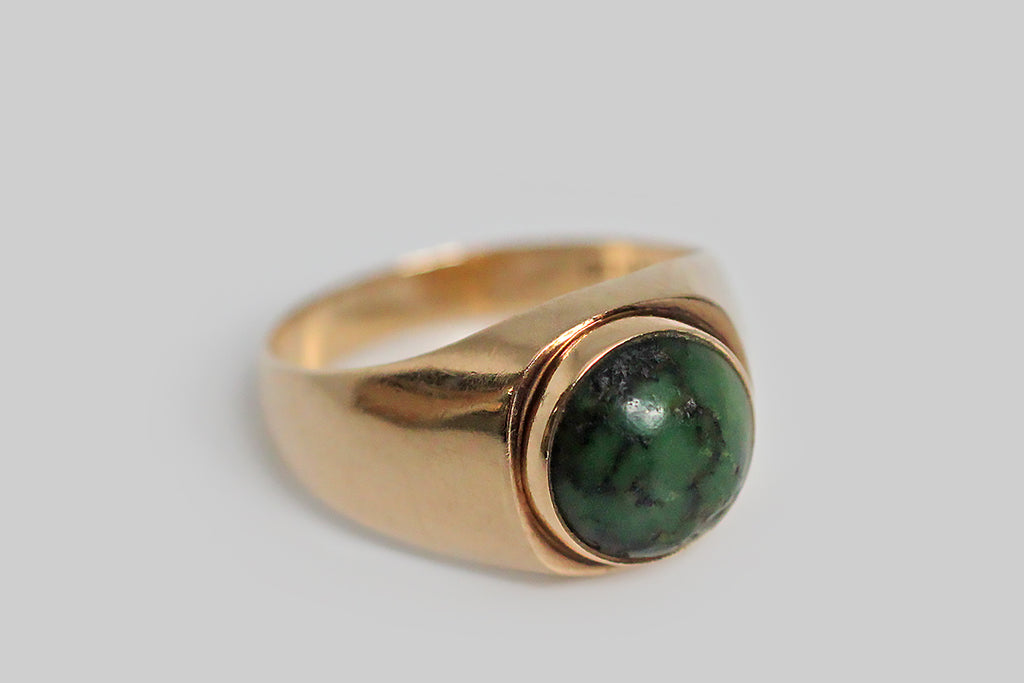A sleek, mid-20th-century, Danish modernist ring, set with a character-rich green turquoise cabochon. This gem is held in a smooth, round bezel, that sits atop the very-slightly-larger cushion-shaped ring face— a subtle design element that makes this ring a little unusual and that gives its design a geometric focus.