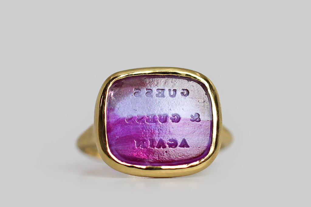 "Playful and quirky, a vibrant, bi-color (violet and lavender) glass seal sits, nested, inside a thick-walled, organic bezel, which tapers seamlessly into the ring's integral shank. This unusual Victorian-era wax seal is carved with the phrase ""guess & guess again""— that coy phrase would have struck the seal's owner pretty funny in the 1800s; taken out of context it is an absurd and challenging mantra"