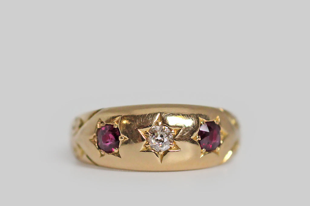 A soulful, Victorian-era, three stone gypsy ring, modeled in 18k yellow gold, whose precise, six-pointed, star-shaped seats hold a trio of gemstones⁠— a chunky, little old mine cut diamond, and a pair of old cut rubies. The ring's shoulders are decorated with an ornate, deeply-engraved arrow motif (to represent that cupid's arrow that struck you and your beloved). All of the ring's engraved elements are expertly hand-executed. This darling is hallmarked for Birmingham and the year 1902.