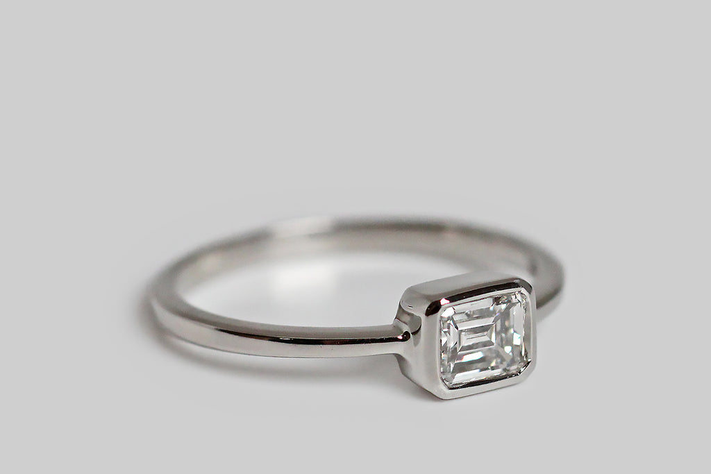Timeless and elegant, a vintage, half-carat, emerald-cut diamond rests east/west, inside a smooth platinum bezel. This smooth bezel has lovely, crisp lines, and it connects seamlessly to the ring's slender, tapering, square-faced shank. This ring is modern, minimalist, and subtly geometric; its vintage diamond is white (G/H) and very clear (VVS), with an especially large table that creates an icy, hall-of-mirrors effect. This ring is made entirely in platinum