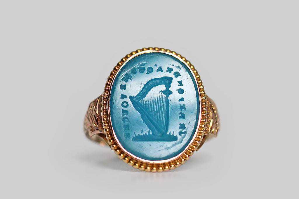 "An especially rare and ephemeral Georgian era signet ring, mwhose turquoise glass intaglio seal is carved with an image of a harp, surrounded by the phrase ""je reponds á qui me touche:"" I respond to every touch. This beautiful old Tassie seal is still partnered with its original high karat gold ring mount."