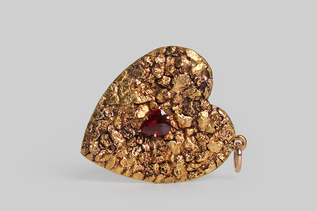 Poor Mouchette | Curated Antique Jewelry, Vintage Jewelry & Engagement Rings | Portland, Oregon | An extra large, Victorian-era heart pendant, covered edge-to-edge in natural gold nuggets. These gold nuggets have a rich, high, gold color, and fascinating organic textures. A sanguine, heart-shaped, garnet doublet rests amid these nuggets, in six, claw-like prongs. The heart's backplate is pierced from 14k gold sheet