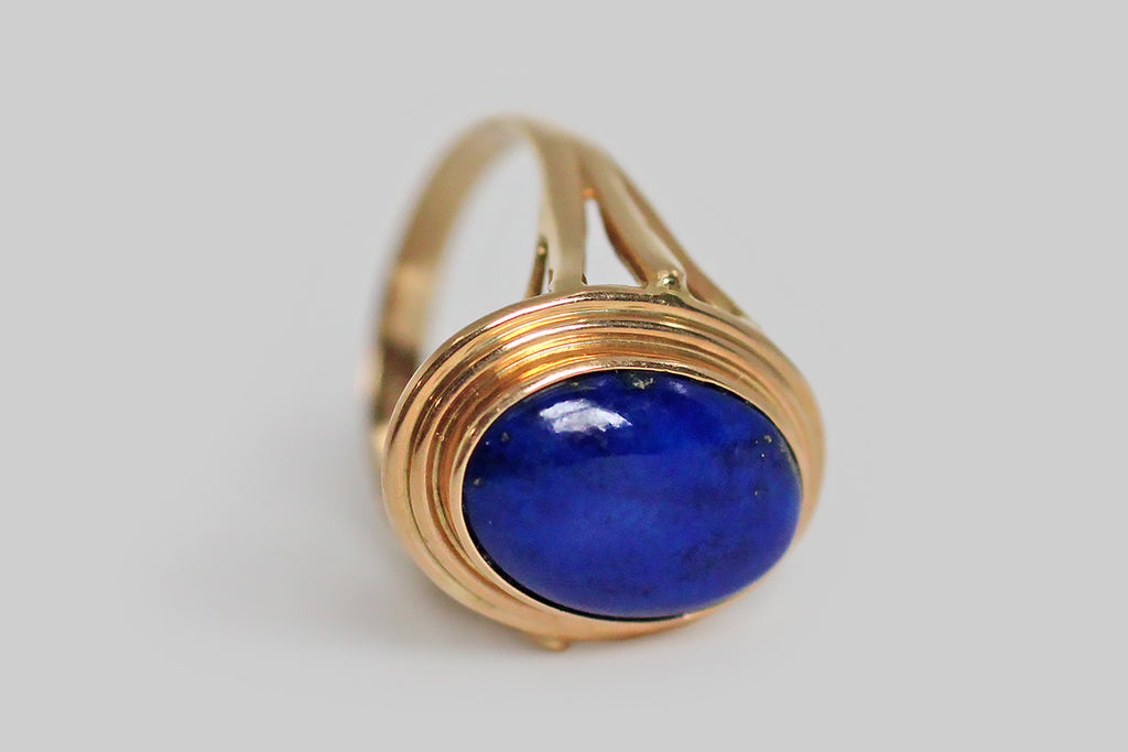 A vibrant, mid-twentieth-century, lapis lazuli ring, modeled in 14k yellow gold, whose large, oval gem is held in a simple, fluted bezel. This ring has split shoulders and an elegant wire work under-gallery that extends the ring's circle-centric vision. The lapis gem is a deeply and evenly saturated blue field, with a few scattered pyrite flecks near the bezel edge— it is every bit as vibrant as it appears, here.