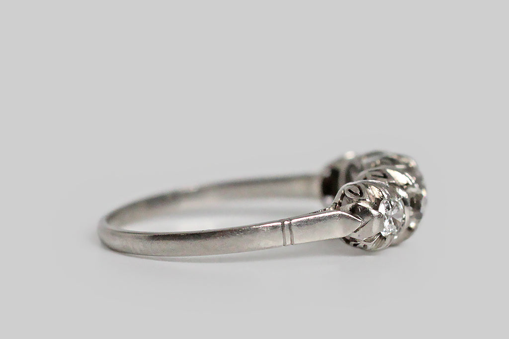 An antique five stone ring, modeled in platinum and set with .75 carats of chunky old cut diamonds. The ring's gallery is decorated with an open-work, lily of the valley/fleur-de-lys motif, and each of its soulful white diamonds has a large open culet. The ring's cathedral shoulder is decoratively notched. Its slender, half-round shank tapers subtly toward the base. This is very flattering in wear and it would make a lovely wedding or anniversary band.