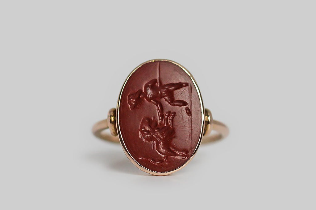 An antique signet ring, made in 18k yellow gold and set with an intaglio-carved jasper stone, which depicts a battle between a lion and a Roman Bestarii. This fight scene was carved into the jasper tablet with a deep, vigorous character. The intaglio is held in a smooth, low-profile bezel, and the ring's shoulders are minimally decorated with a charming crescent-shaped detail. This ring's shank is fully round.