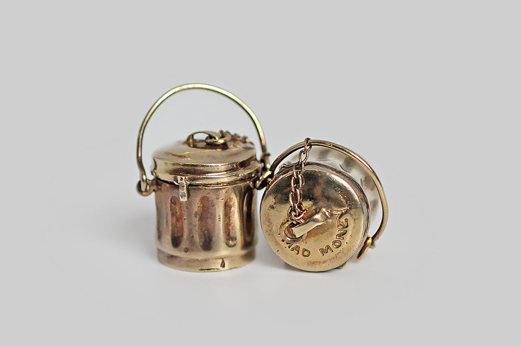 "An unusual, matched pair of mad money charms, each a tiny, realistic trash can, with a removable lid and a glass bottom, through which tightly rolled paper money can be seen. The little lids are engraved with the phrase ""mad money"" and are connected to the can handles by a fine curb chain. Mad money charms were a popular mid century idea, but this particular form is really uncommon— if you find these adorable mad cans at all, you find them without their rolled up dough."