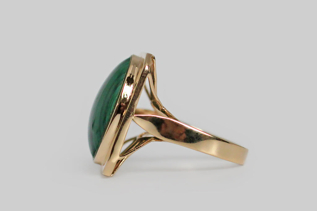 A mid twentieth century cocktail ring, with geometric sensibilities, modeled in 14k yellow gold. This ring's bold, rectangular face has clipped corners— it functions, visually, as a frame for the ring's vibrant, striped, oval, malachite gem. The ring's under-gallery is a careful arrangement of round wires that extend, ray-like, from the its face. The flat-wire shank features a lance-tip, cathedral shoulder. Marked 14k and 585 for purity.