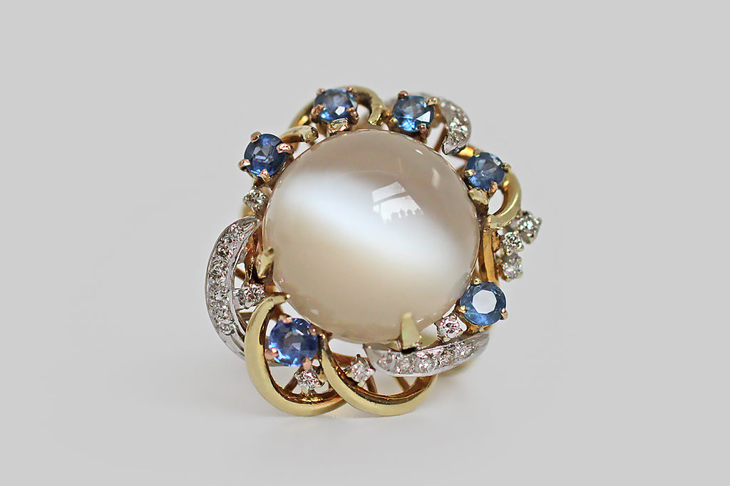 A glorious, mid 20th century, moonstone cocktail ring, made in 14k gold. The ring's big, high-dome, cat's eye moonstone cabochon displays a strong milk and honey quality, and its adularescence is mesmerizing. This central gem is held in four claw-like prongs; it sits inside an elaborate nest of curling, briar-like, gold forms, some of which are pave-set with small diamonds.