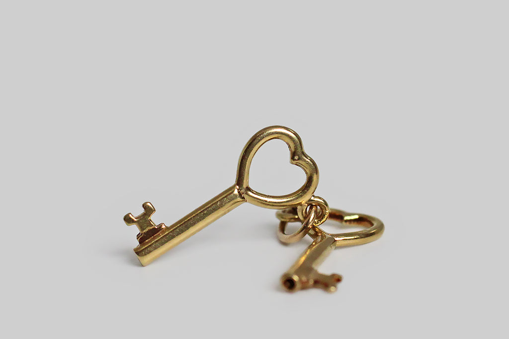 "A very sweet mid 20th century charm, modeled in 14k yellow gold, whose subject is a miniature pair of keys, with heart shaped tops. These little keys hang separately on their jump ring, and jangle pleasantly with movement. There's the classic ""keys to my heart"" reading available here, but because there are two keys present, and only one person holds them, we also have a little room for alternative symbolic"