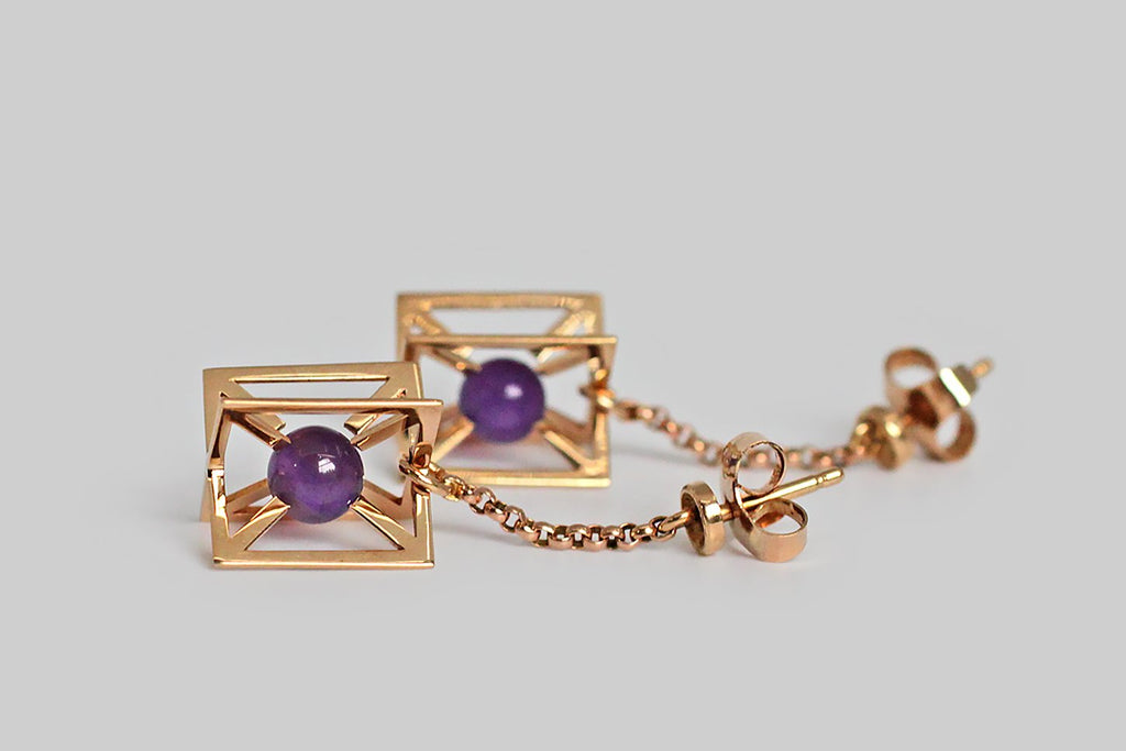 A very cool pair of mid-twentieth century earrings, made in 14k rose gold, each taking the form of two intersecting panels that come together to form a three-dimensional cage. Betwixt these panels, where the centermost point would be, a small amethyst sphere is suspended. This sphere moves freely within the limited space.