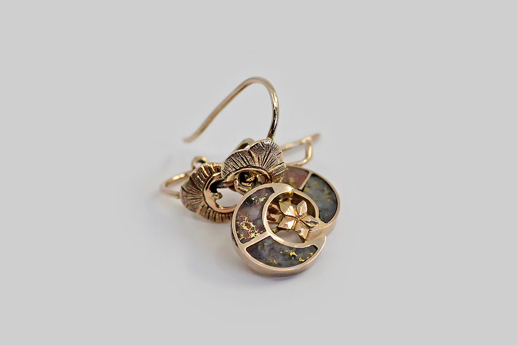 A pair of Victorian-era moon and stars drop earrings, whose little crescents are inlaid with both rose and grey colored gold bearing quartz. A faceted five-pointed star nests in the curve of each moon, and both celestial forms dangle below a small lobed crescent shape that (because of its orientation) reads like a miniature crown or headdress. These darlings are magical and unusual survivors from the era, especially considering their dainty scale. Metal is 12k rosy yellow gold. The hook shaped ear wires are