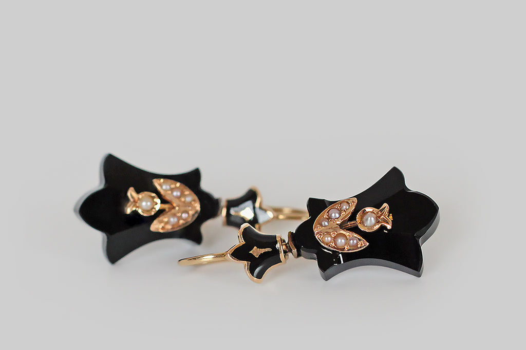 An elegant pair of Victorian-era mourning earrings, whose shield-like, fleur-de-lis-shaped drops are carved from natural jet. These shapely plaques are each decorated with a single, 14k gold, seed-pearl-set, lily of the valley blossom. These earrings have locking, kidney wires that attach to their enameled tops. These tops are hinged where they meet the drops, and the construction is beautiful! A special pair of antique earrings that are suitable for frequent wear.