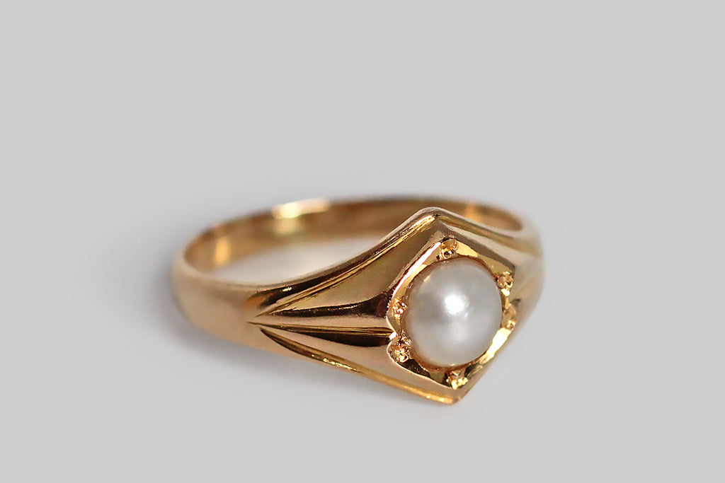 A shapely, mid-twentieth-century ring, modeled in 18k yellow gold and set with a luminous, white, button-shaped, saltwater pearl. This ring's perfectly balanced form is two-peaked, with simple, deeply-carved shoulder details that are reminiscent of folded paper or fabric. This is simple, elegant, and mystical-seeming, bearing some resemblance to anthroposophical designs. T