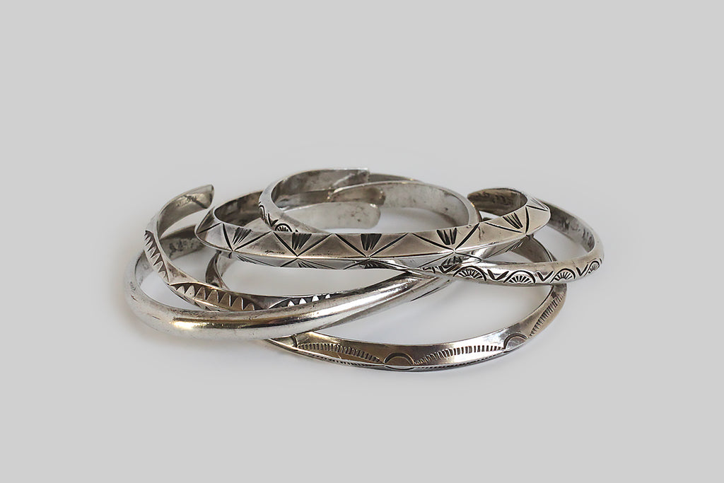 A set of five, slender 1970s cuff bracelets, made in sterling silver and hand stamped with decorative symbols— we see what might be interpreted as sun rays, rattlesnake jaws, and thunderbird tracks. Three of these cuffs have a peaked knife-edge profile, and two are half-round. One is polished and undecorated for contrast. These bracelets make a lovely sound in wear and came to us as a set. They appear to be Native American made.