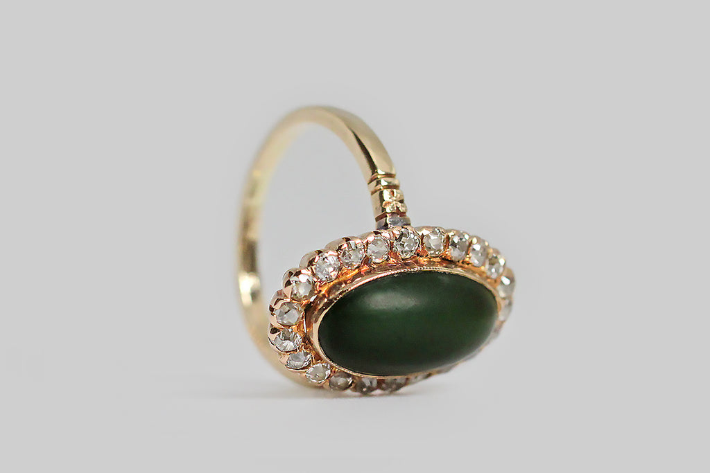 A Victorian-era ring, whose satiny, oval, nephrite jade cabochon is encircled by a halo of the loveliest old mine cut diamonds. These old darlings have the tall presence and tiny tables that give them their unique, soulful character; their exquisite sparkle, set against the soft, opaque nephrite is especially winning. The jade cabochon is set in a milgrain bezel.