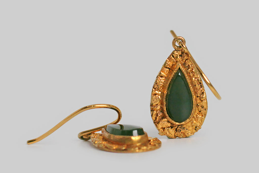 A dainty pair of teardrop-shaped, mid 20th century earrings, whose flat-top, nephrite jade cabochons are surrounded by a deep border of natural gold nuggets. These small, richly-textured placer nuggets are carefully arranged on the earrings' 10k gold base. The teardrops swing below a simple pair of shepherd's hook earwires