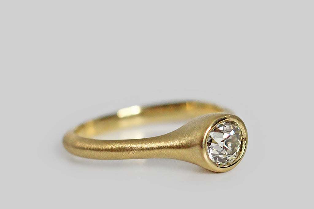 Soulful and sparkling, an antique, .70 carat old mine cut diamond sits, nested, inside a thick-walled, organic bezel, which tapers seamlessly into its ring's integral shank. This ring is modern and organic— its graceful shape is reminiscent of the beautiful pixie cup lichens (Cladonia asahinae). Metal is 18k yellow gold; it is delicately brushed. Old mine cut diamonds are much loved by collectors for their unique, hand-cut character, their small, high, tables, open culets, and off-round shape.