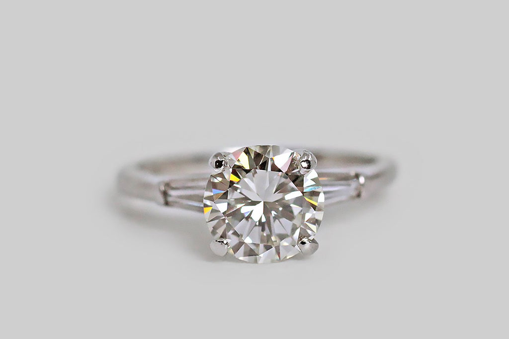 A mid 20th century diamond engagement ring, designed to reflect the tastes of the Art Deco era. This timeless beauty is made in platinum, and its central 1.75 carat, vintage, brilliant-cut diamond is held aloft in a four prong basket setting. The ring's shoulders are accented with a pair of tapered baguette diamonds. This ring is bold and minimal, and the glamorous central diamond is full of heart-winning fire.