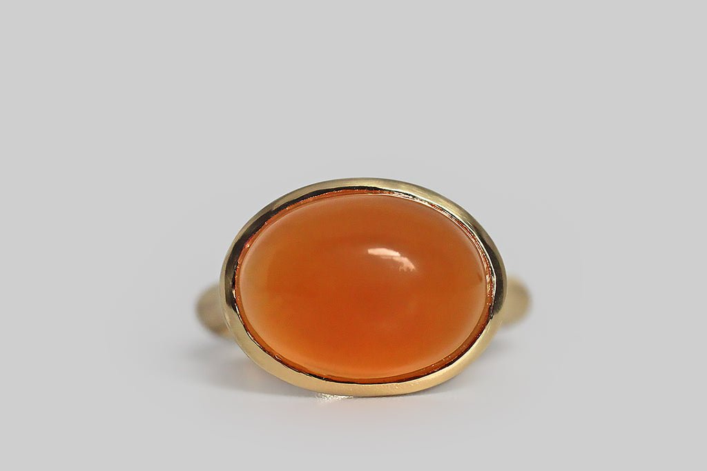 Jubilant and glowing, a vibrant orange chalcedony cabochon sits, nested, inside a thick-walled, organic bezel, which tapers seamlessly into its ring's integral shank. This ring is modern and organic— its graceful shape is reminiscent of the beautiful pixie cup lichens (Cladonia asahinae). Metal is 18k yellow gold; it is delicately brushed.  This ring was entirely handcrafted in Portland, OR, by collaborating, independent craftspeople and designers— even the cabochon was cut locally.