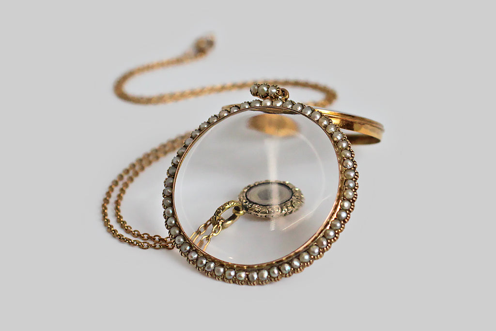 An antique gold locket, made on a grand scale, with a magnifying lens, and a delicate halo of fifty-two, collet-set seed pearls. This airy darling opens easily at the base of the backside, which nests snugly inside the bezel of the front-piece. The locket's large bail is set with three further pearls. This locket is all original. The design is slim and feminine, a perfect frame for whatever treasure is placed inside— a lock of hair, a photograph, a scrap of fabric, a handful of diamonds or colored gems.
