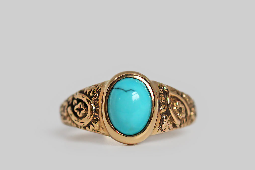 The Periapt ring, modeled 14k yellow gold, in the image of a beloved Victorian era jewel, and featuring a brilliant-blue, Sleeping Beauty turquoise cabochon. Our Periapt ring is so-called because its carved decor is a collection of lucky charms: a horseshoe, a wishbone, and a handful of four leaf clovers . . . a spattering of cheerful flowers flesh out the design. This ring is substantially made, with a classic tapering profile, and its turquoise gem is bezel set. It is ideal for frequent wear.