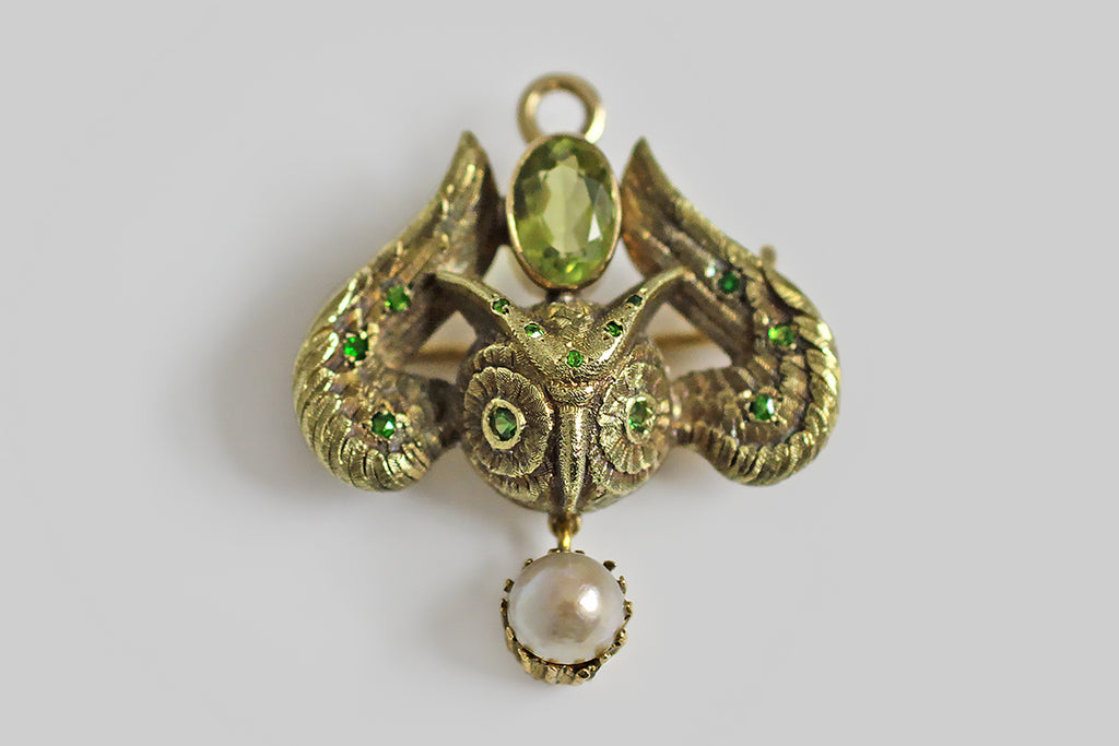 "A Victorian-era watch pin, with a folding pendant bail, modeled in the form of a horned owl with up-stretched wings. The owl is is beautifully realized, with fine carving to represent the fibers in each of his feathers. Between the curving wings, and betwixt his ""horns"" a large peridot is held in a broad smooth bezel. Small demantiod garnets are scattered, in nested bead settings, across his face and wings, and two more are set into his eyes."