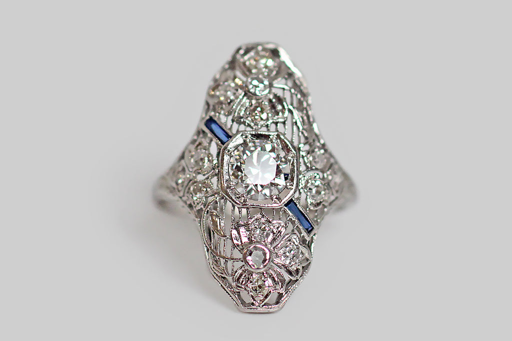 A beautiful and unusual platinum dinner ring, whose filigree setting features a pair of airy diamond-set clovers, one bending gracefully to the right, the other to the left. These lolling clovers frame the ring's central .65 carat old European cut diamond, while a pair of French cut sapphires lay behind the central diamond, on the diagonal, like a sash. This shapely ring is very low profile and lays along the finger like a shield, covering the space between the first and second knuckle.